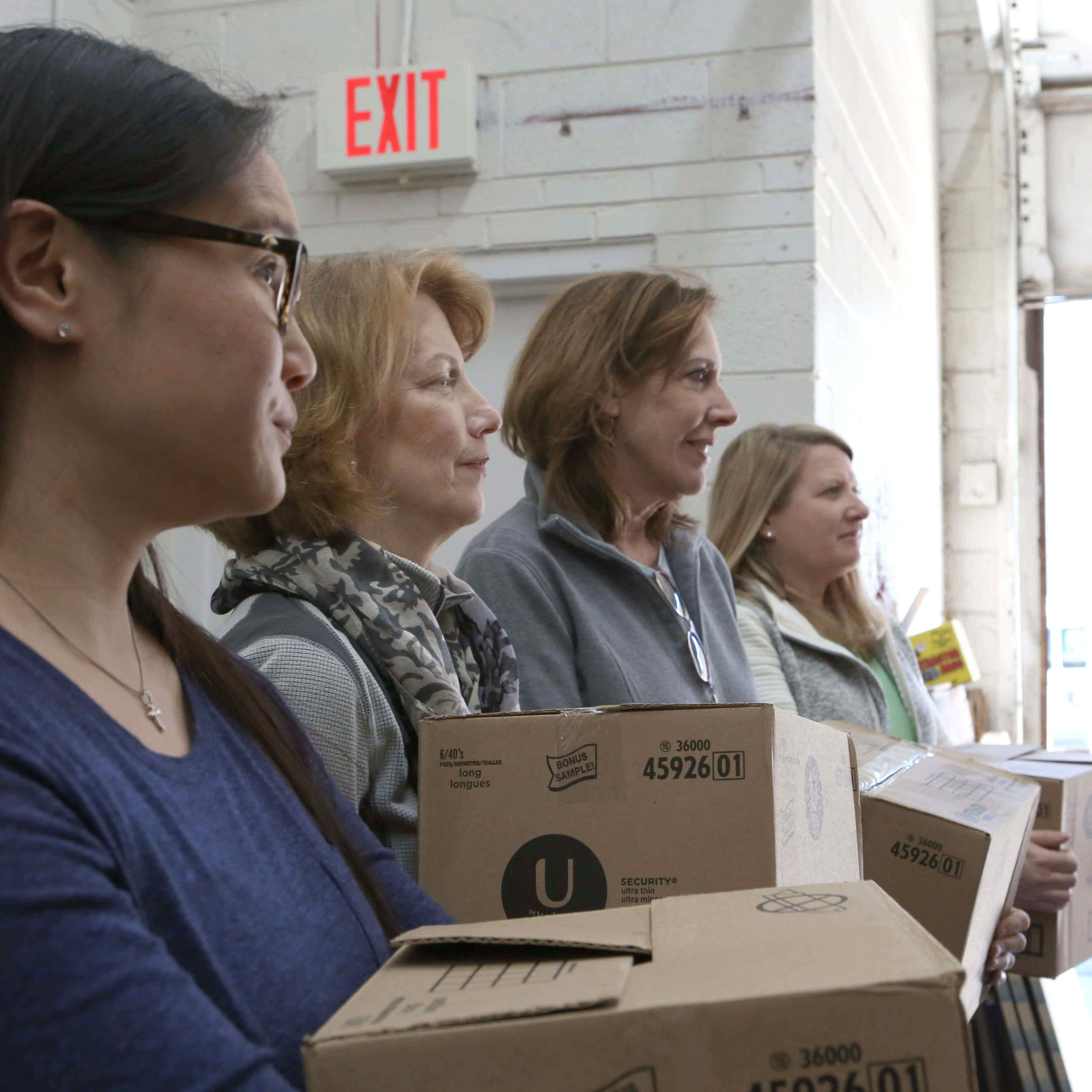 Volunteers hold boxes of U by Kotex tampons, pads, and liners that are ready to ship to women in need