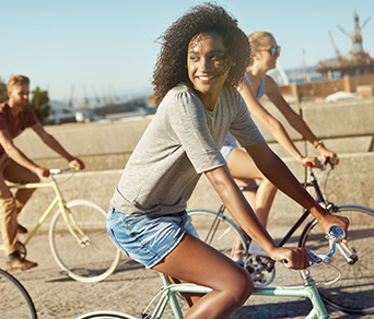 A woman riding a bicycle on the beach with friends
