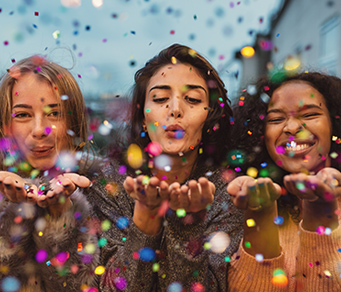 Women blowing confetti