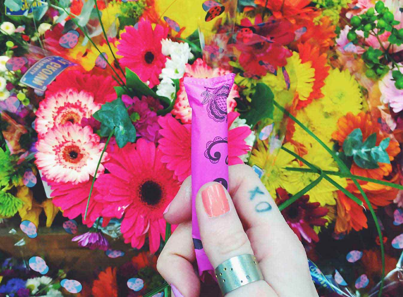 Girls hand holding tampon over bed of flowers