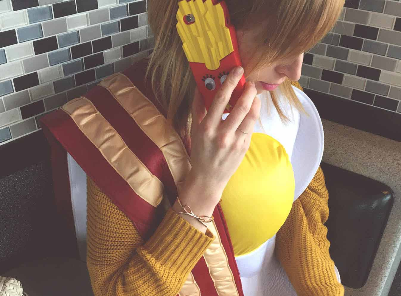 Girl in egg costume talking on mobile phone with french fry case