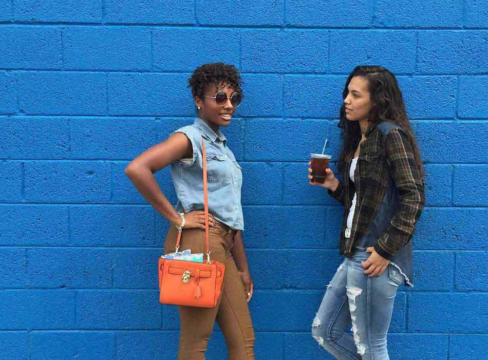 Two girls leaning on blue wall talking