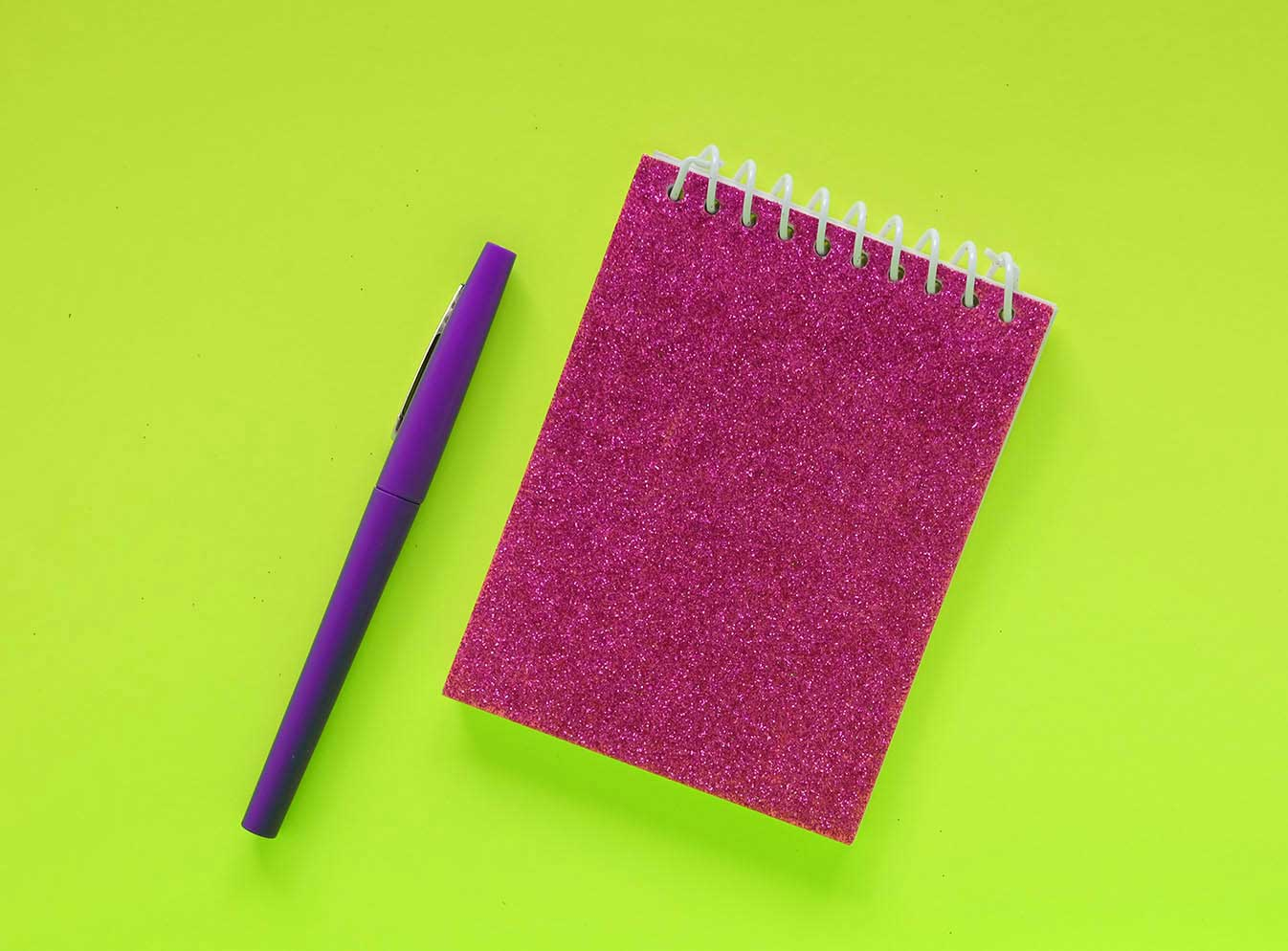 Notepad and pen on green background