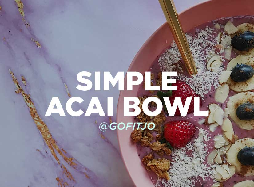 Bowl of healthy fruits, granola, acai, nuts, and seeds on table. Simple Acai Bowl recipe.