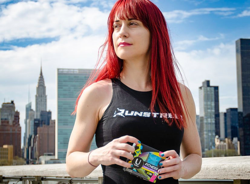 Woman with red hair outside wearing fitness apparel holding UbyKotex product. City skyline in background.