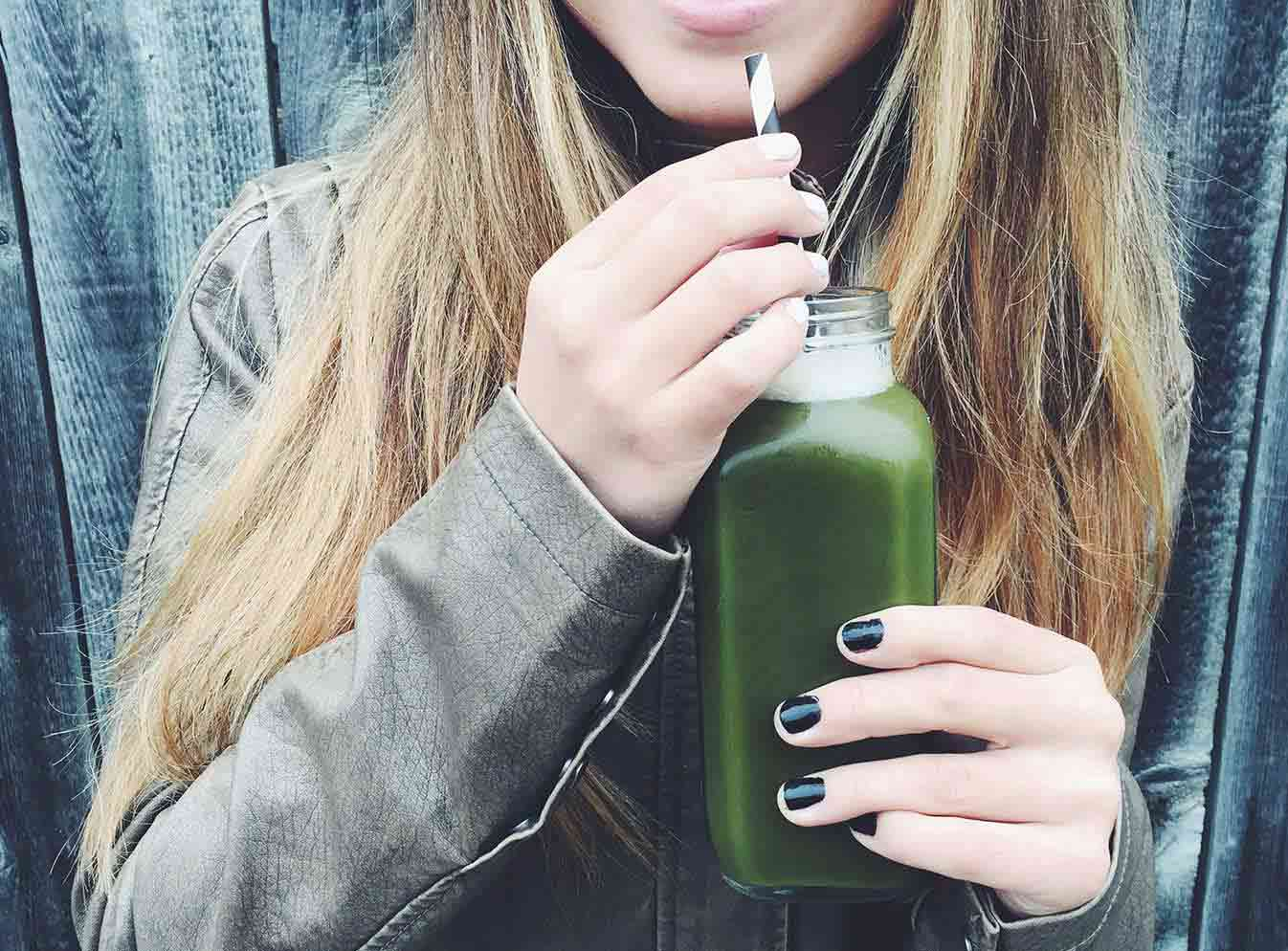 Girls hand holding pressed juice bottle