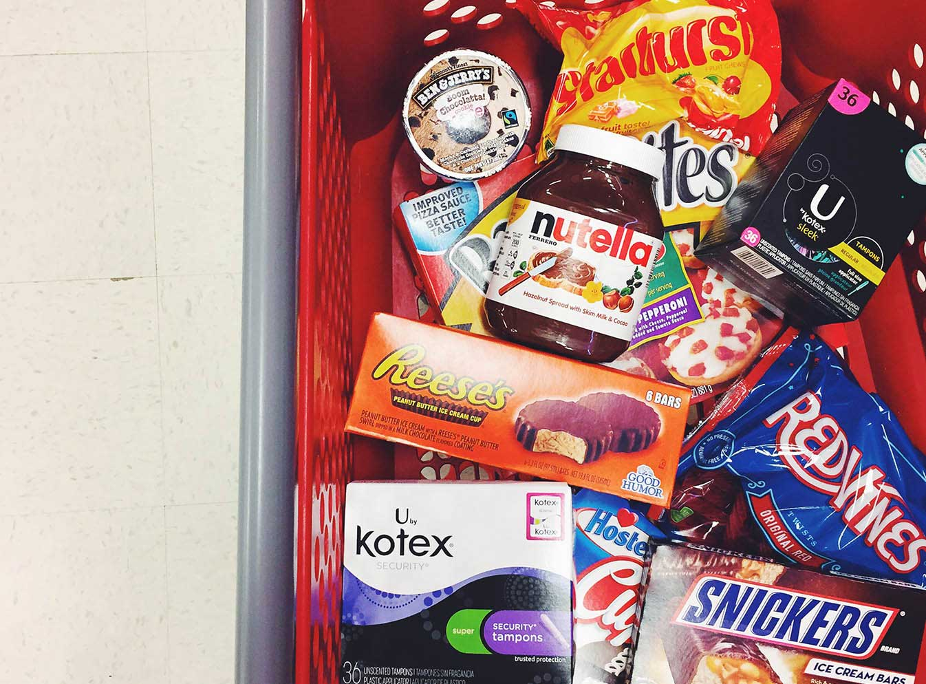 Shopping cart full of chocolate, candy, snacks, and U by Kotex