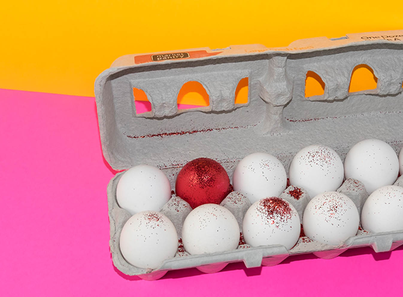 Carton of eggs with one red egg