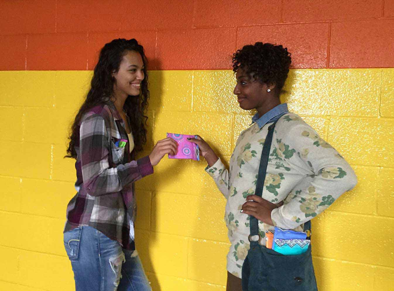 Girl handing pad to friend leaning on yellow wall