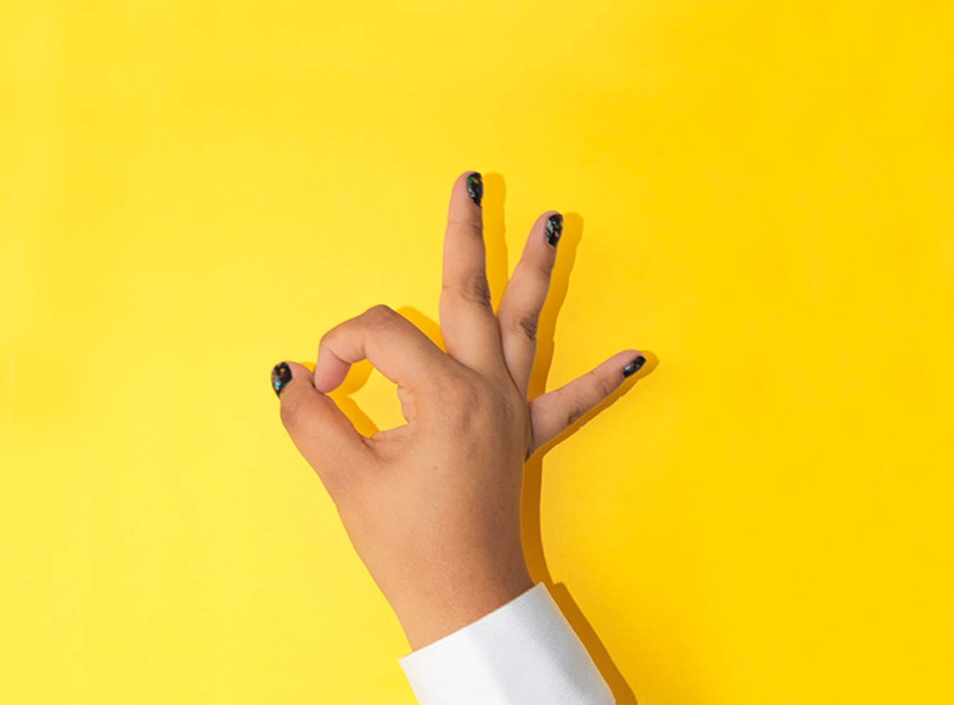 Hand making OK sign on yellow background