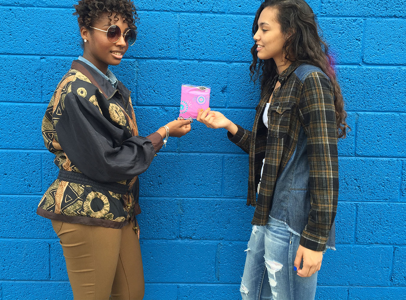 Two girls leaning on a blue wall handing over a pad